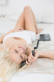 Relaxed smiling woman using telephone in bed
