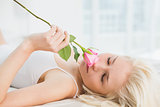 Close up of pretty young woman in bed with a rose