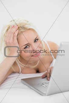 Casual relaxed blond with laptop in bed
