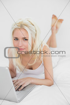 Casual relaxed young blond with laptop in bed