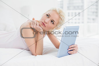 Thoughtful casual blond with tablet PC lying in bed