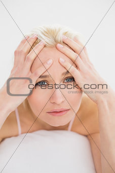 Close up of a tensed young woman in bed