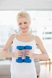 Thoughtful woman with dumbbells at fitness studio