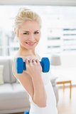 Smiling woman with dumbbell at fitness studio