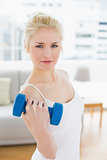 Serious woman with dumbbell at fitness studio
