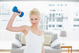 Woman with dumbbell at fitness studio