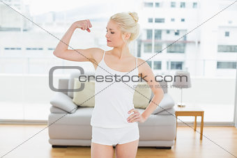 Fit woman flexing muscles in fitness studio