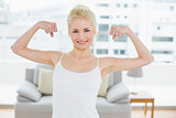 Fit woman in sportswear flexing muscles in fitness studio