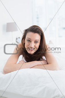 Close up portrait of pretty happy woman resting in bed