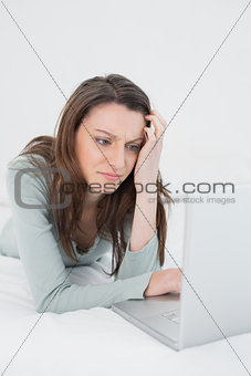 Casual sad young woman using laptop in bed