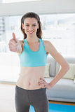 Toned woman gesturing thumbs up in fitness studio