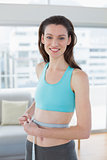 Toned woman in sportswear measuring waist in fitness studio