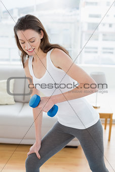 Fit woman exercising with dumbbell in fitness studio