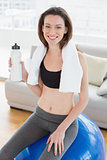 Woman sitting on exercise ball with water bottle in fitness studio