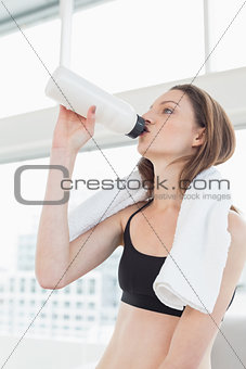 Fit woman with towel around neck drinking water in fitness studio