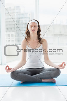 Toned woman in lotus pose with eyes closed at fitness studio