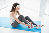 Toned woman wearing shoes on exercise mat at fitness studio