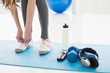 Woman tying shoes with sporty equipment on floor