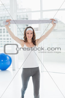 Fit young woman holding up towel in a fitness studio