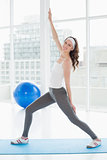 Portrait a fit woman stretching hand in fitness studio