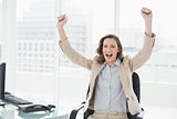 Elegant businesswoman cheering with hands raised in office