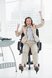 Businesswoman cheering with hands raised in office