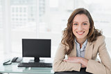 Elegant smiling businesswoman sitting at office desk
