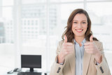 Elegant smiling businesswoman gesturing thumbs up in office