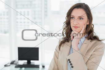 Thoughtful elegant smiling businesswoman in office