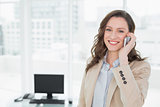 Elegant businesswoman using mobile phone in office