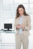 Elegant businesswoman text messaging in a bright office