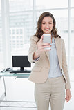 Elegant businesswoman text messaging in office