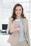 Smiling elegant businesswoman text messaging in office