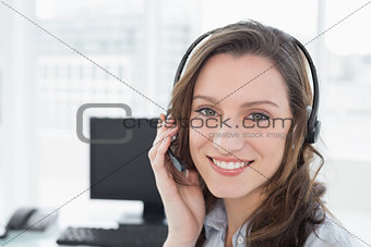 Portrait of businesswoman wearing headset in front of computer