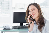 Smiling businesswoman using phone in front of computer