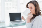 Businesswoman drinking coffee in front of laptop in office