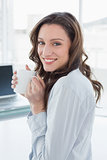 Businesswoman with coffee cup in front of laptop in office