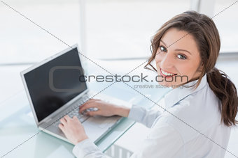 Smiling brown haired businesswoman using laptop in office