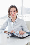 Elegant businesswoman with laptop and diary in office