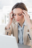 Businesswoman suffering from headache in front of laptop