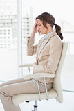 Side view of businesswoman suffering from headache in office