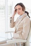 Portrait of businesswoman suffering from headache in office