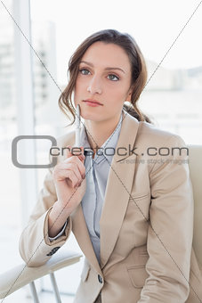 Thoughtful elegant businesswoman with pen in office