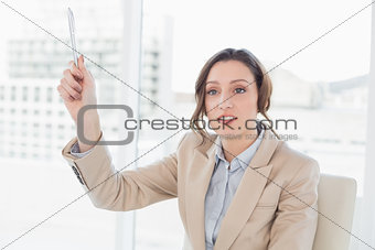 Thoughtful elegant businesswoman with a pen in office