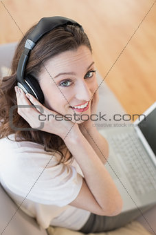 Casual woman using laptop while enjoying music at home