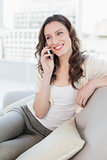 Relaxed young woman using cellphone on sofa