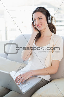 Casual woman using laptop while enjoying music on sofa