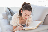 Relaxed casual woman reading a book on sofa