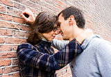 Portrait of love couple outdoor looking happy against wall backg