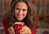 Smiling young woman in christmas red dress having cup of hot cho